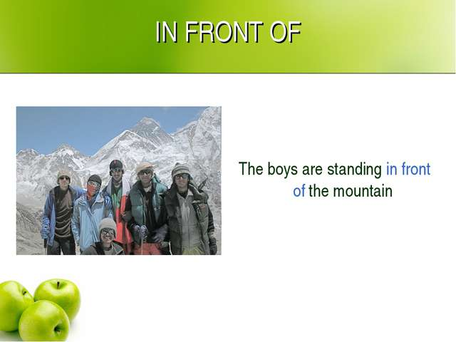 IN FRONT OF The boys are standing in front of the mountain