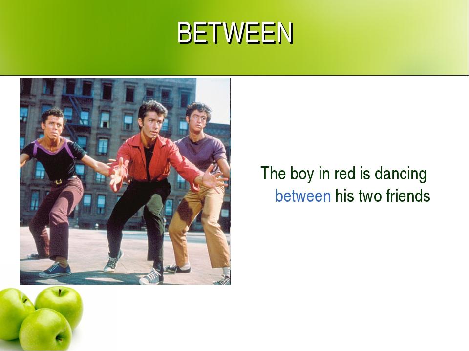 BETWEEN The boy in red is dancing between his two friends