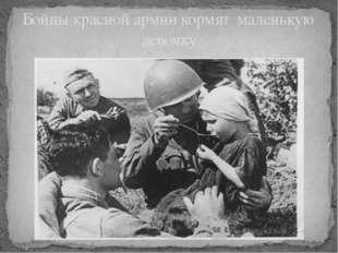 Бойцы красной армии кормят маленькую девочку
