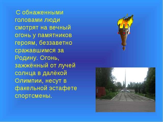 С обнаженными головами люди смотрят на вечный огонь у памятников героям, без...